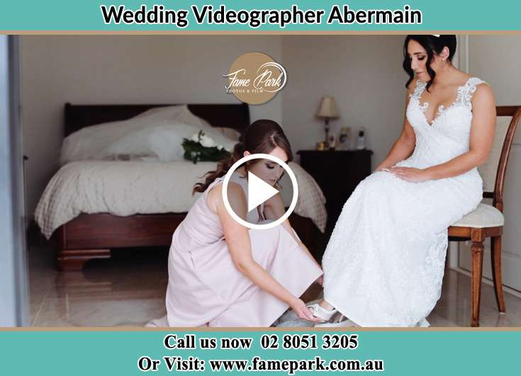 A girl putting the wedding shoes on the Bride's foot Abermain 2326