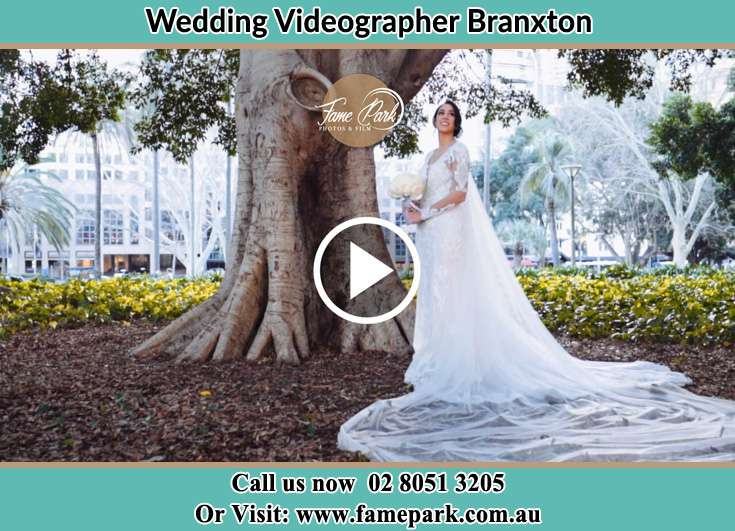 The Bride holding a bouquet of flowers under a tree Branxton NSW 2335