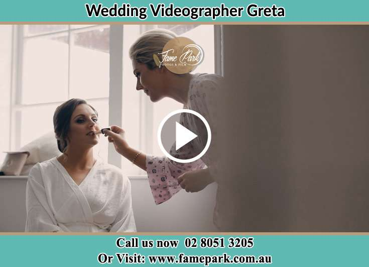 A woman applying lipstick to the Bride Greta NSW 2334