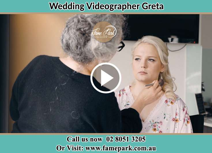 A woman applying makeup to the Bride Greta NSW 2334