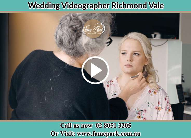 A woman applying makeup to the Bride Richmond Vale NSW 2323